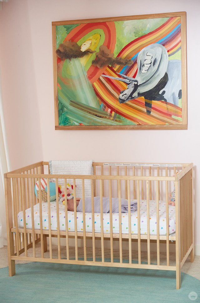 A colorful painting of a dinosaur hangs over a crib in this children's room.