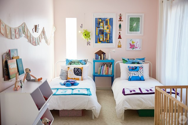 This children's room design includes two twin beds, a crib, lots of books, and original artwork.