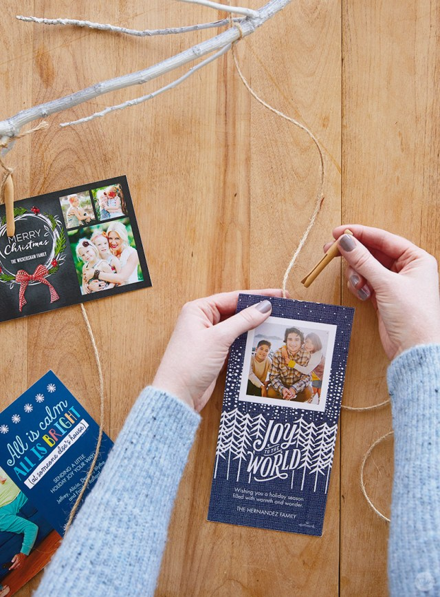 Using a clothespin to attach holiday greetings to a Winter branch Christmas card holder