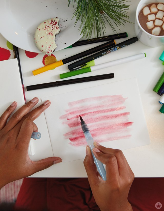 Using a brush marker to paint a background on an envelope