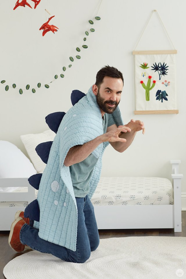 Colin W. models the Dino Spine Blanket from the Dinos and Botanicals collection from Hallmark Baby