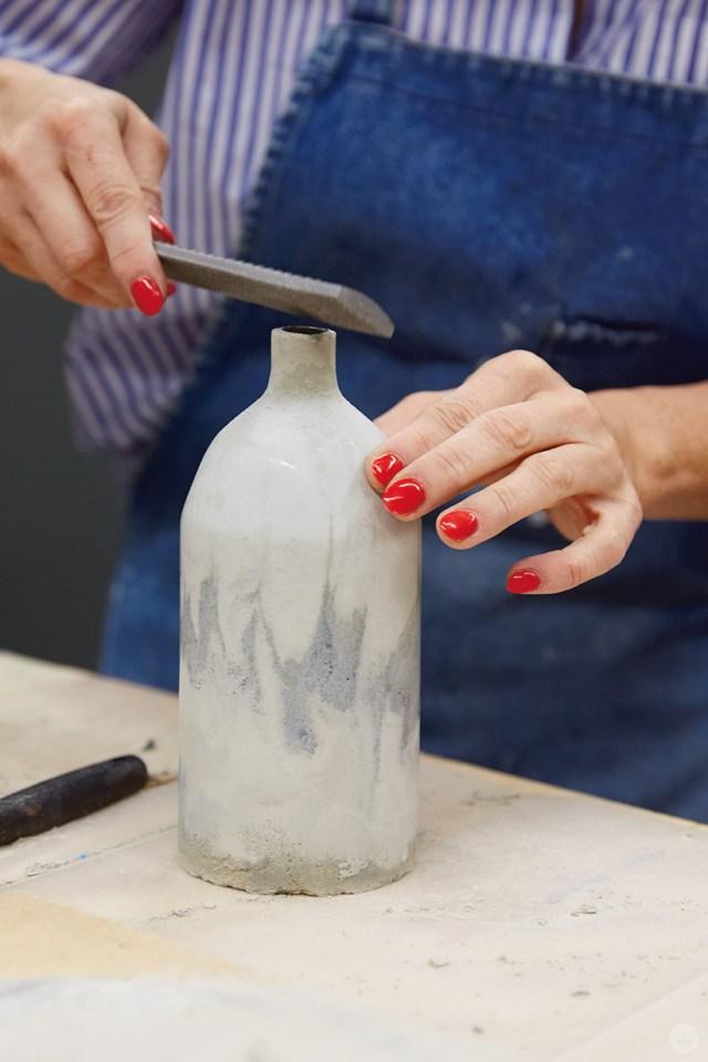 Sanding the neck of a concrete vase