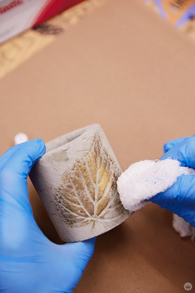 Application de cire métallique sur un vase en béton