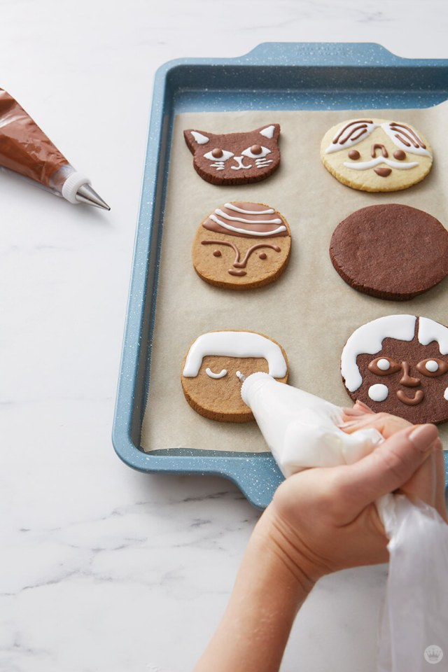Drawing eyes on a gingerbread face with royal icing. | thinkmakeshareblog.com