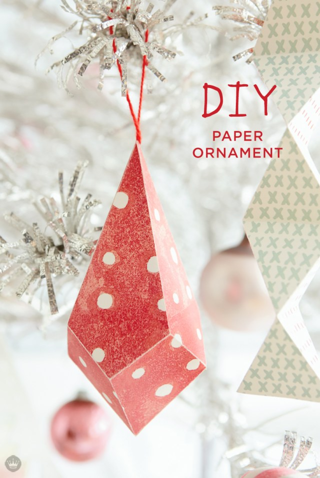 Red and white patterned paper ornaments hanging in Christmas tree.