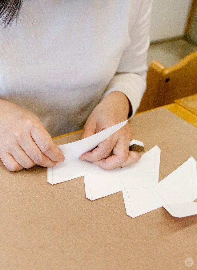 Folding the template for your DIY Christmas paper ornaments.