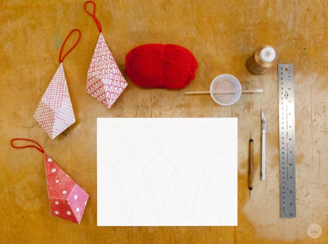Red and white patterned paper ornaments supplies on tabletop.