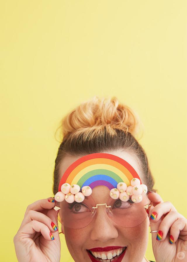 Hallmark Designer Katie K. wearing DIY Pride Sunglasses with a rainbow and pink pom pom clouds | thinkmakeshareblog.com