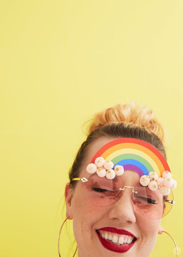Happy person wearing DIY Pride Sunglasses with a rainbow and pink pom pom clouds | thinkmakeshareblog.com