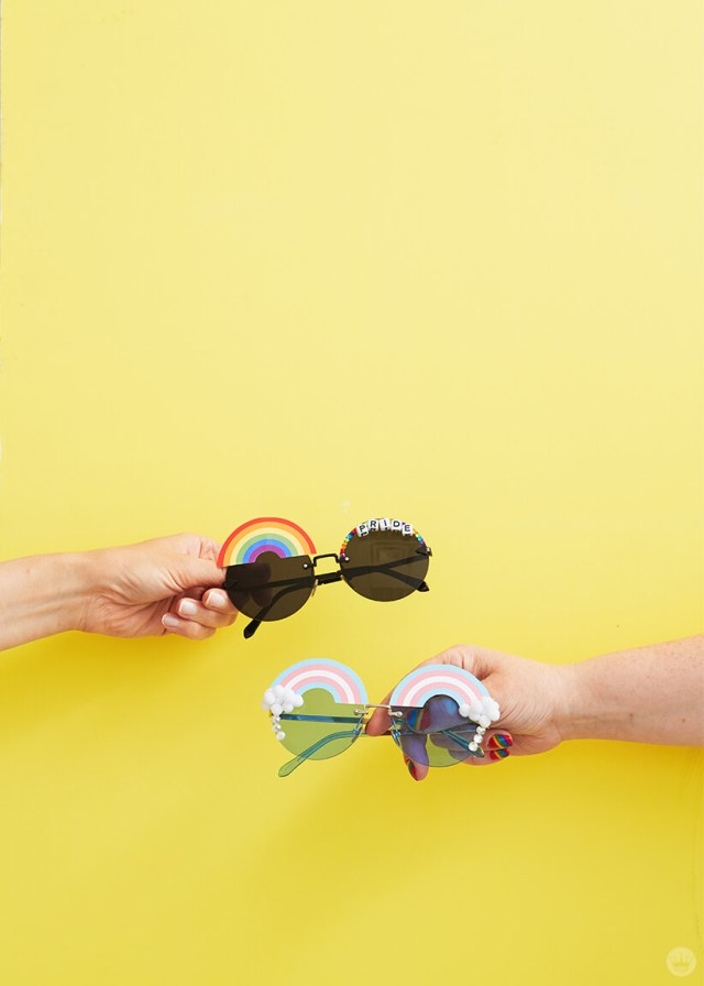 Two arms holding DIY pride sunglasses on a yellow background | thinkmakeshareblog.com