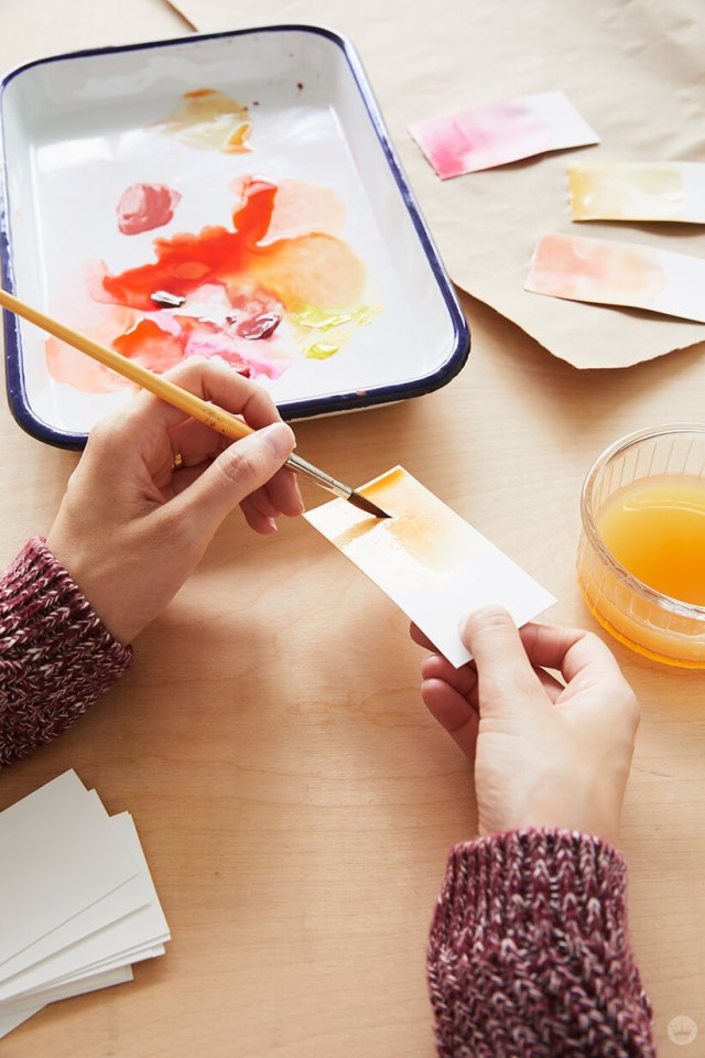 Adding paint to a surface flooded with water for dip-dye Thanksgiving place cards | thinkmakeshareblog.com