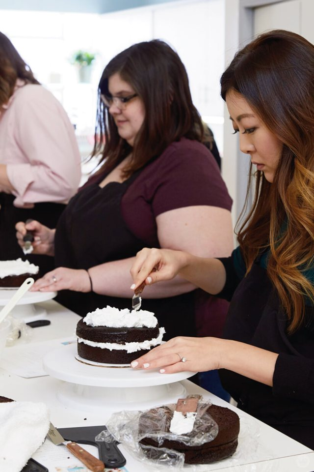 Artists in the initial stages of their Easter cake ideas: frosting a chocolate layer cake