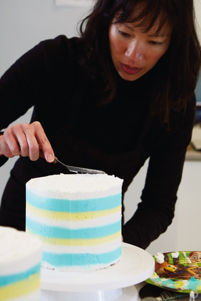 Smoothing the cake top for Easter cake ideas with stripes and chocolate bunnies