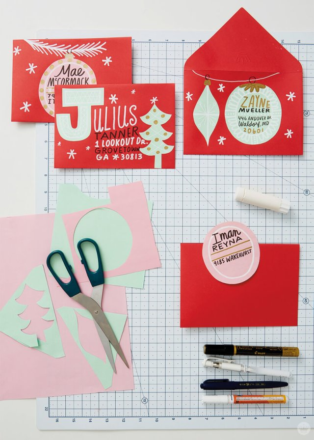 Cut paper designs on Christmas card envelopes—red and pink ornaments, letters and trees with black, gold and white accents. | thinkmakeshareblog.com