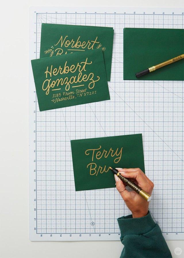 Bold and gold hand-lettered addresses on dark green envelopes. | thinkmakeshareblog.com