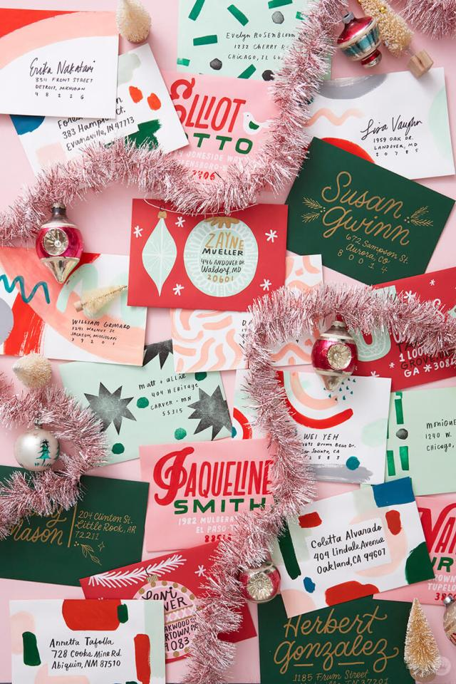 A pile of decorated Christmas mail art—envelopes in different colors with hand lettering, cut paper, painted swooshes, and more. | thinkmakeshareblog.com