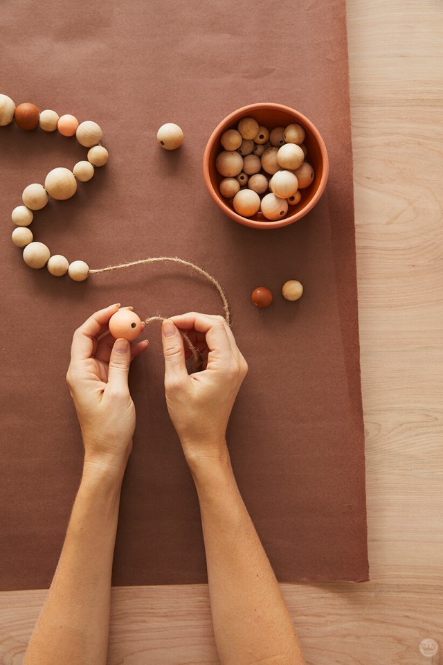 Stringing wooden beads onto twine for the DIY fall bead garland | thinkmakeshareblog.com