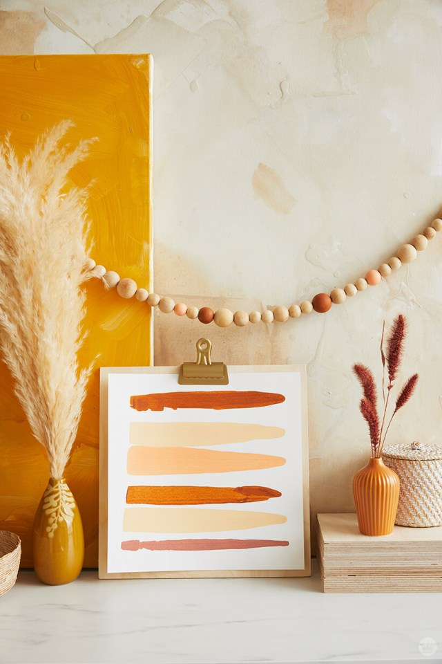 Fall painted stripes art with wooden bead garland and pampass grass | thinkmakeshareblog.com