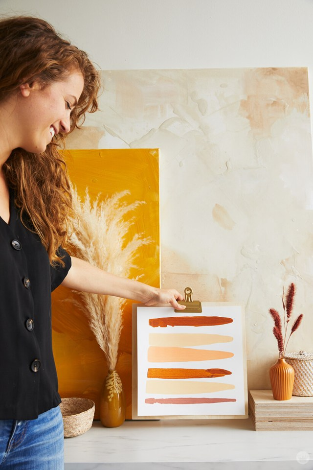 A woman stages the wall art on a table top | thinkmakeshareblog.com