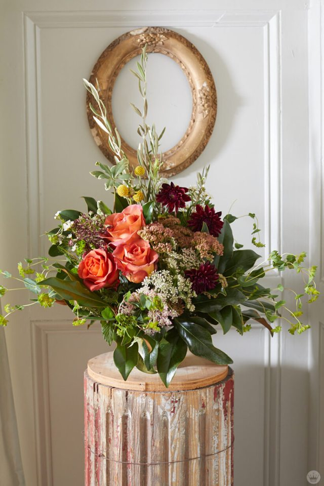 Fall flower arrangement on a weathered pedestal