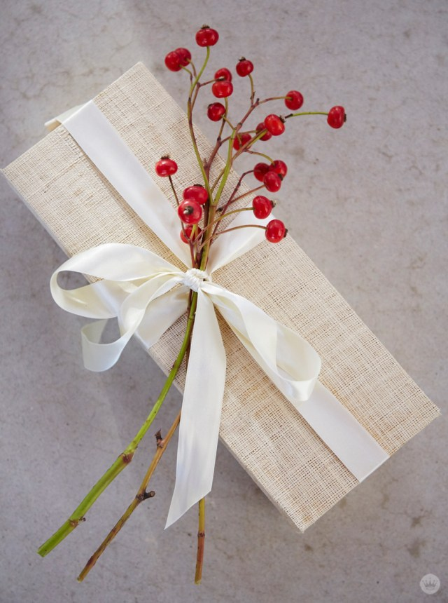 Easy holiday gift giving tips from a Hallmark stylist. Red berries to adorn gift box.