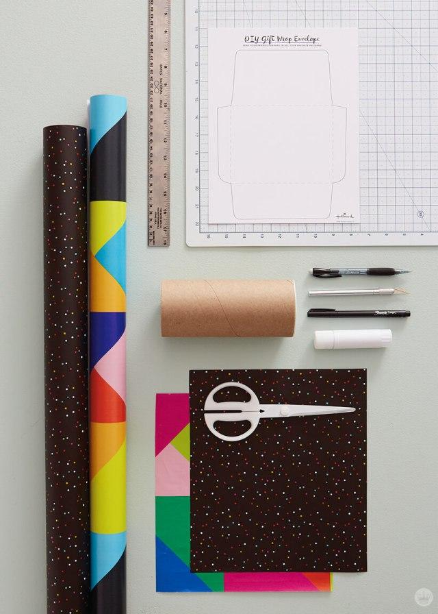 Supplies for mail art ideas: printable template, cutting mat, pens, craft knife, glue stick, scissors, gift wrap.