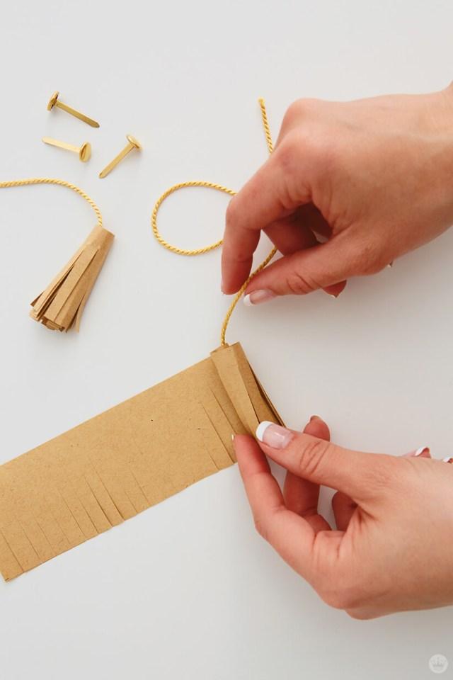 rolling up the fringed paper tassel for the Mini Graduation Gift | thinkmakeshareblog.com