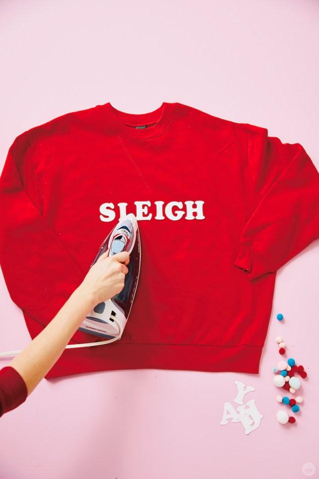 Ironing on felt letters to a red sweatshirt | thinkmakeshareblog.com
