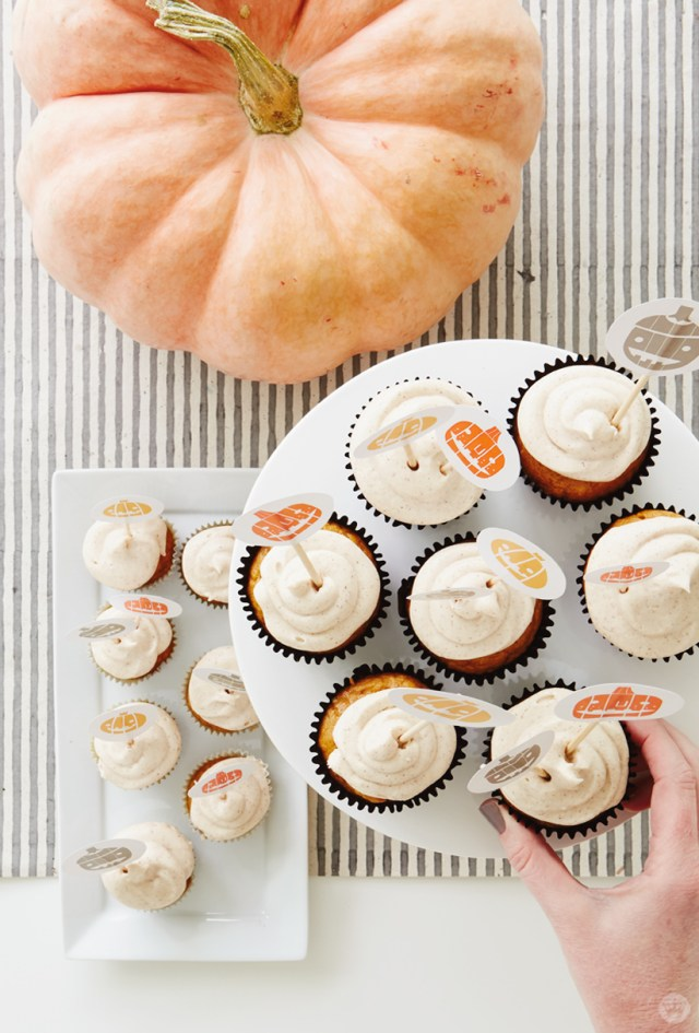 Graphic Jack O'Lanterns in gray, orange, and yellow decorate our free Halloween cupcake toppers. Shown in our pumpkin spice cupcakes with cinnamon cream cheese frosting.