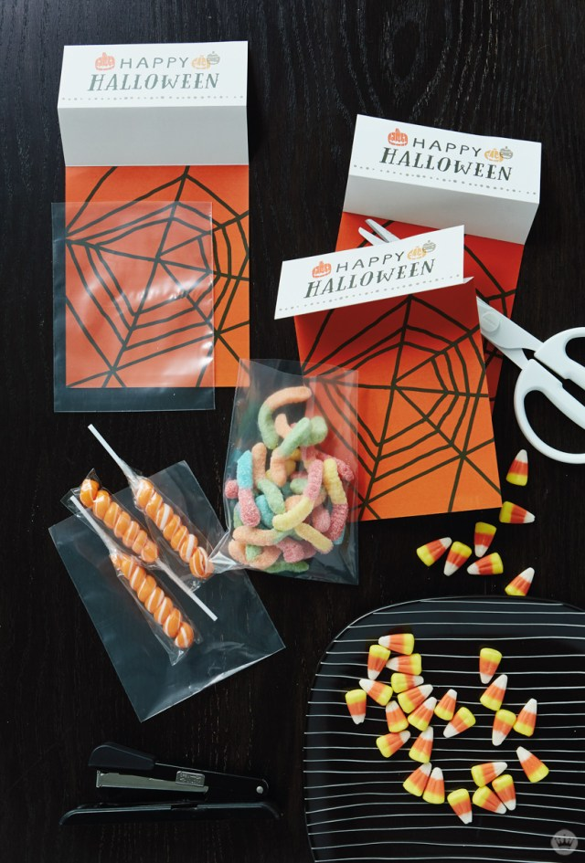 Free printable Halloween treat sacks, shown being assembled and filled with candy corn, gummy worms, and swirly lollipops.