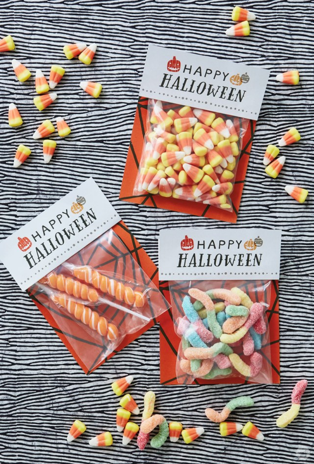 Free printable Halloween treat sacks, shown assembled and filled with candy corn, gummy worms, and swirly lollipops.