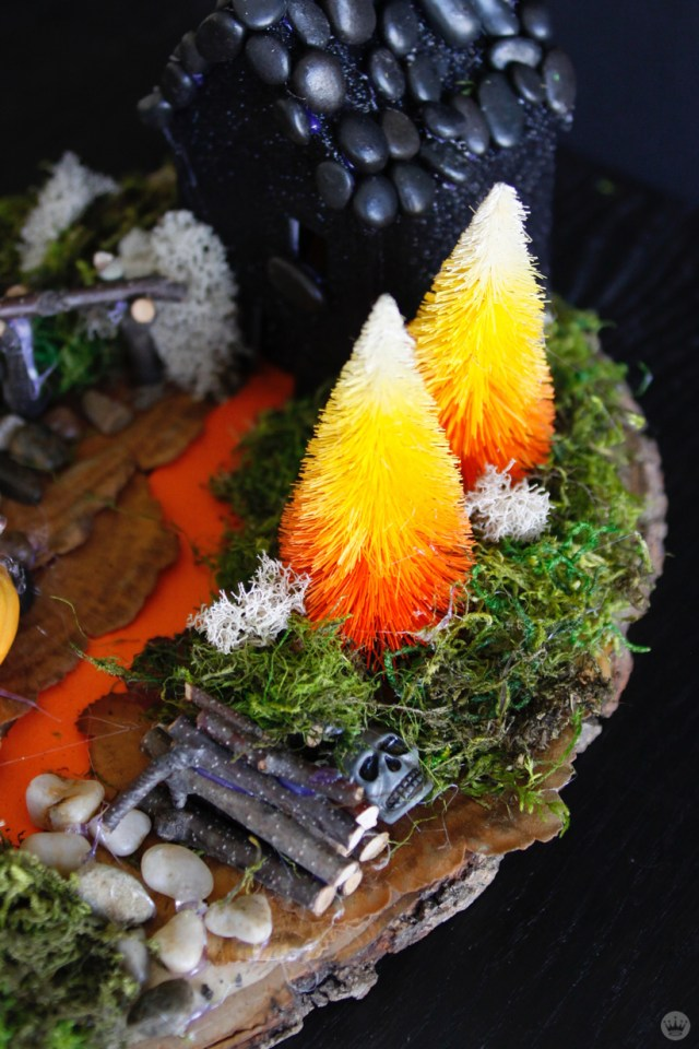 Miniature Haunted House Halloween decorations: One-story house with black paint and pebbled roof. Landscape includes candy-corn-color trees, wooden fence, jack o'lantern garden, and woodpile with hidden skull. (Close up on woodpile.)