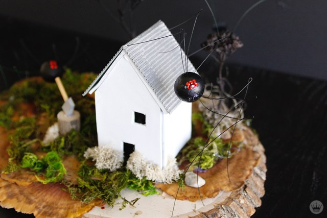 Miniature Haunted House Halloween decorations: Completely ordinary white farmhouse with corrugated roof and wood-splitting stump. Also, it's being overrun by giant spiders and bats.