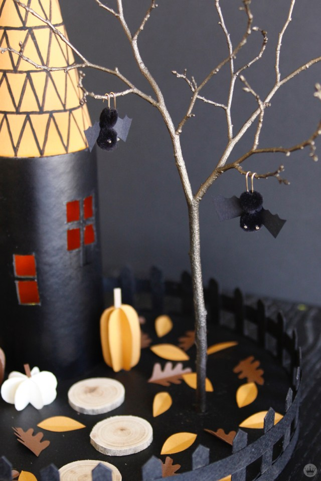 Miniature Haunted House Halloween decorations: Black tower with gold roof covered in triangle pattern, with a pom=pom owl perched on the weather vane on top. Two pop-pom bats hang from a tree, and cut-paper pumpkins and leaves are scattered in the yard.