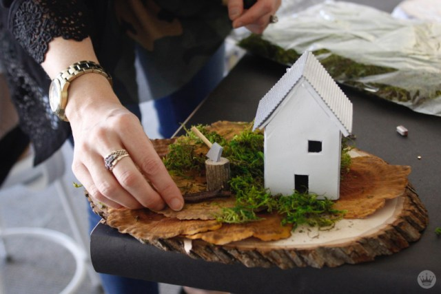 Miniature Haunted House Halloween decorations: White clay house with corrugated roof next to a stump with a tiny ax in it.