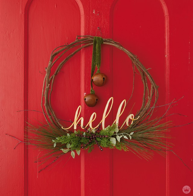 "Modern Christmas wreath ideas: Asymmetrical wreath with bell and laser-cut ""hello"""