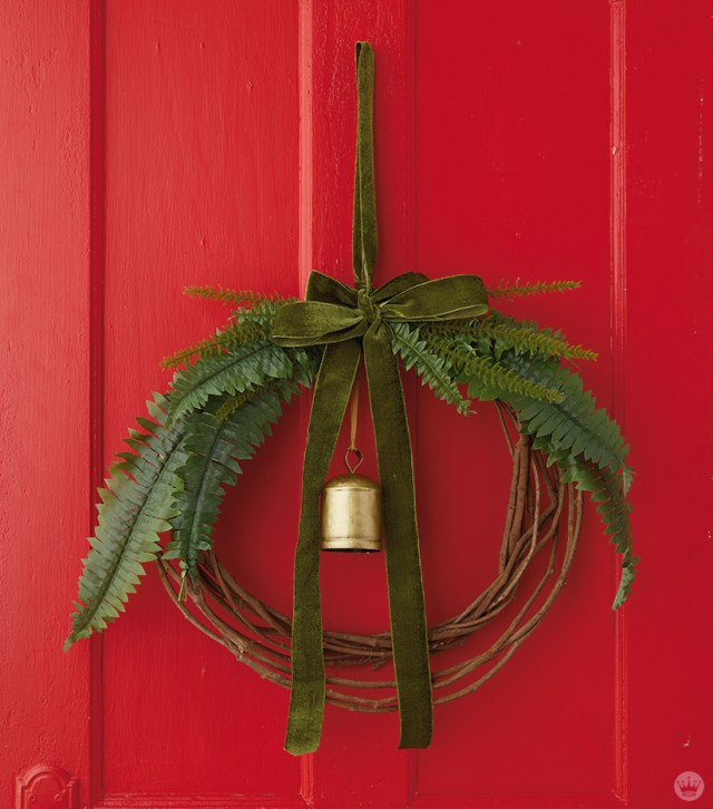 Modern Christmas wreath ideas: Grapevine wreath with ferns, green ribbon, and brass bell