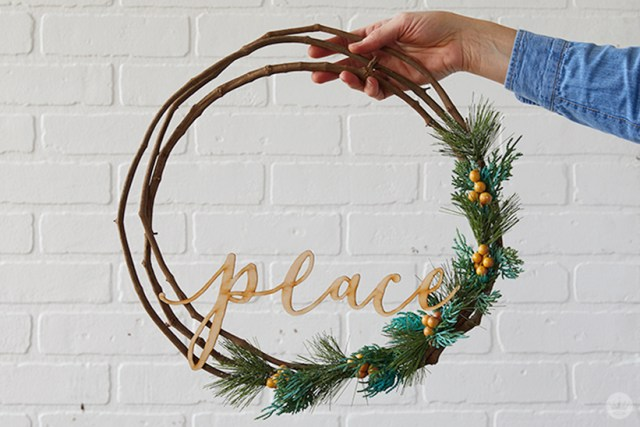 "Modern Christmas wreath ideas: Asymmetrical wreath with laser-cut ""peace"""