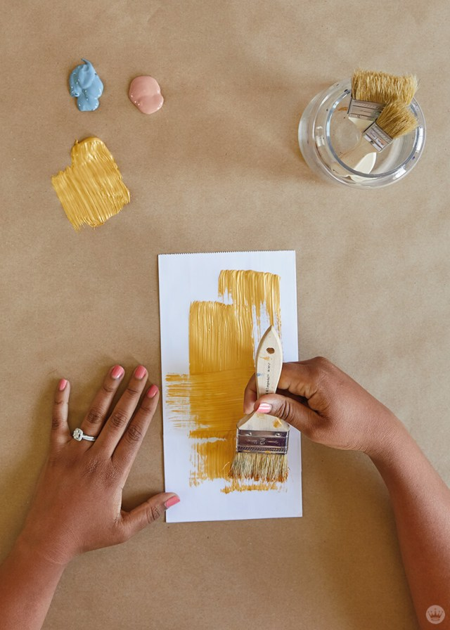 Painting gold acrylic on a white lunch sack for the DIY Paper Plant Bags | thinkmakeshareblog.com