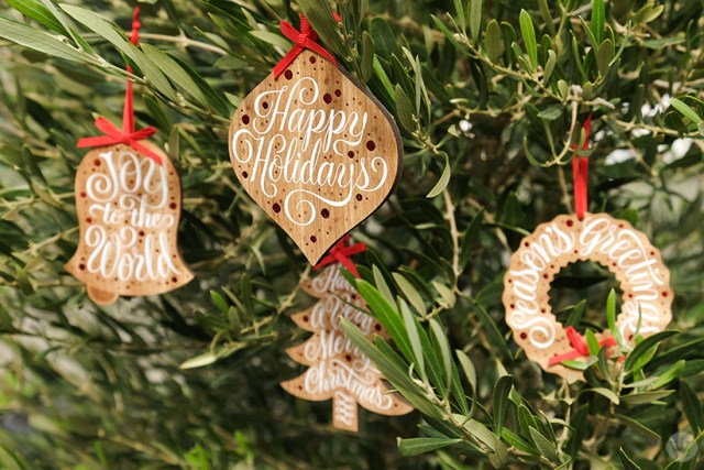 Four wooden ornaments from Jessica Hische Signature collaboration hang on a tree.