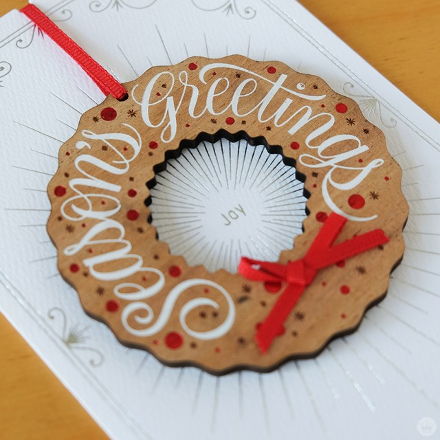 Wooden wreath ornament on white card with foil accents.