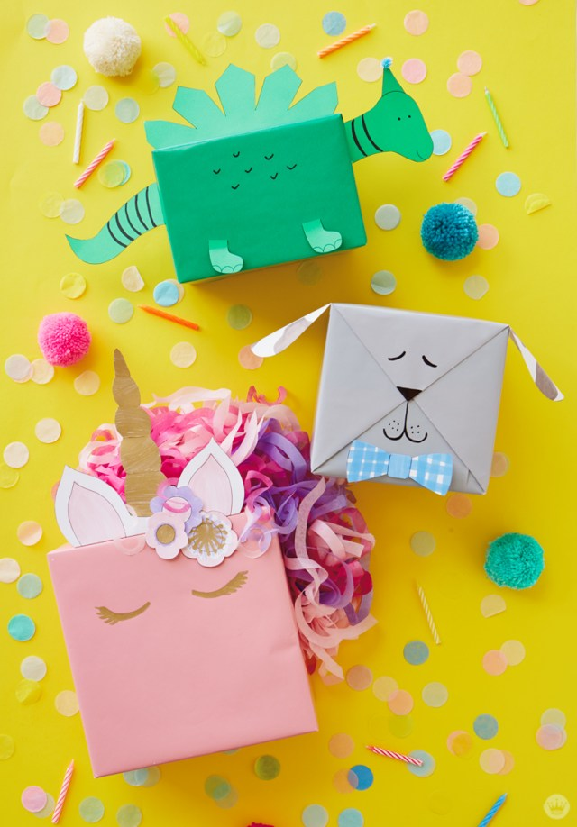 Three kids gift wrap ideas: a green dinosaur, gray dog, and pink unicorn