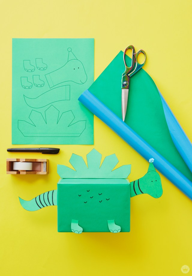 Kids gift wrap idea: dinosaur head, feet, tail, and spine printed on green copier paper, green/blue reversible gift wrap, tape, scissors, pen, and complete wrapped gift.
