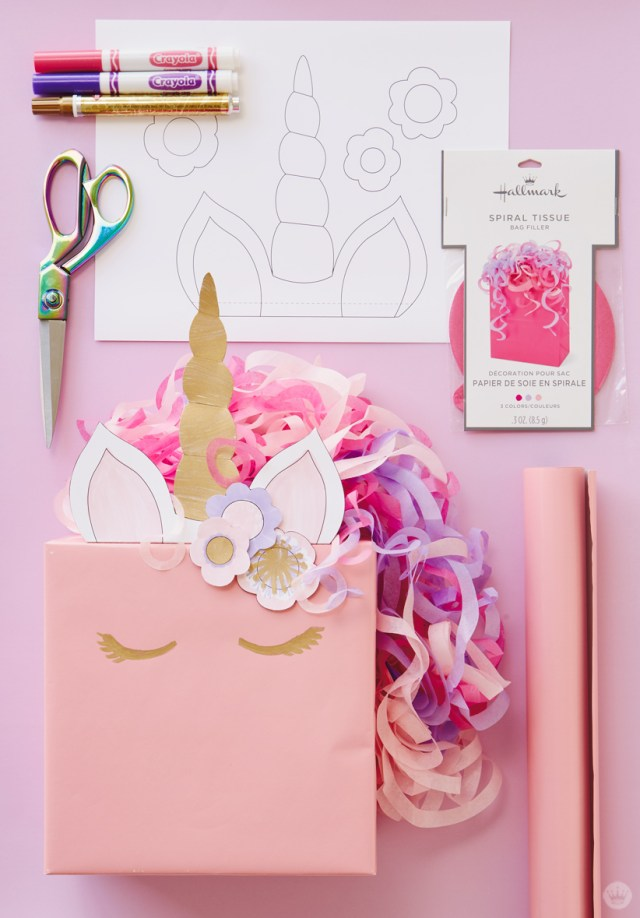 Kids gift wrap idea: unicorn ears, horn and flowers printed on white copier paper, tape, scissors, pink, purple, and gold markers, pink and purple spiral tissue, and complete wrapped gift.