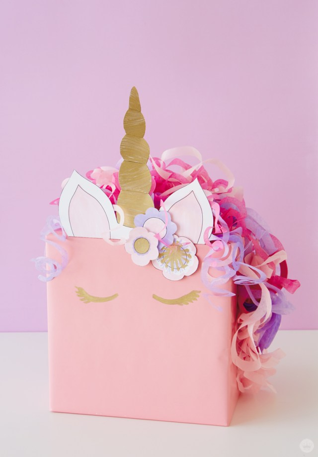 Kids gift wrap idea: Pink box decorated with attachments to look like a unicorn.