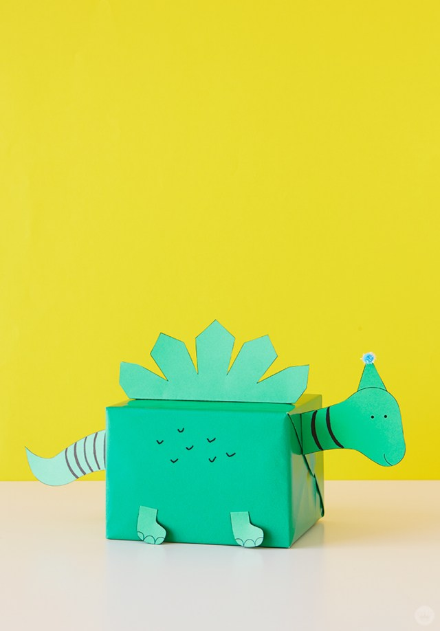 Kids gift wrap idea: present wrapped in green paper with attachments to make it look like a dinosaur.