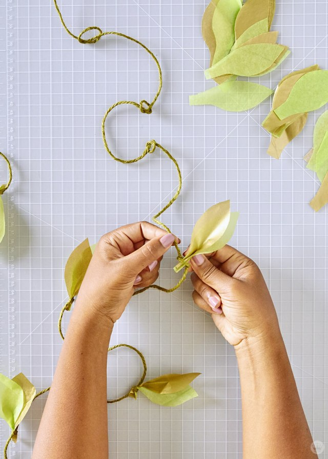 attaching paper leafs to the twine for the DIY paper vine garland | thinkmakeshareblog.com