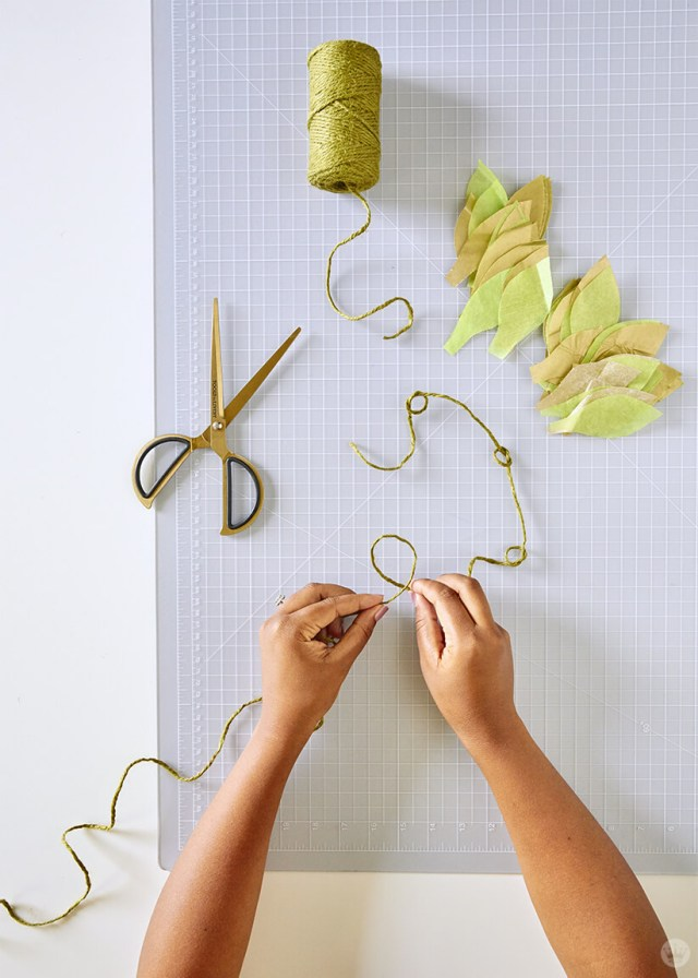 Adding knots to the twine for the DIY paper vine garland | thinkmakeshareblog.com