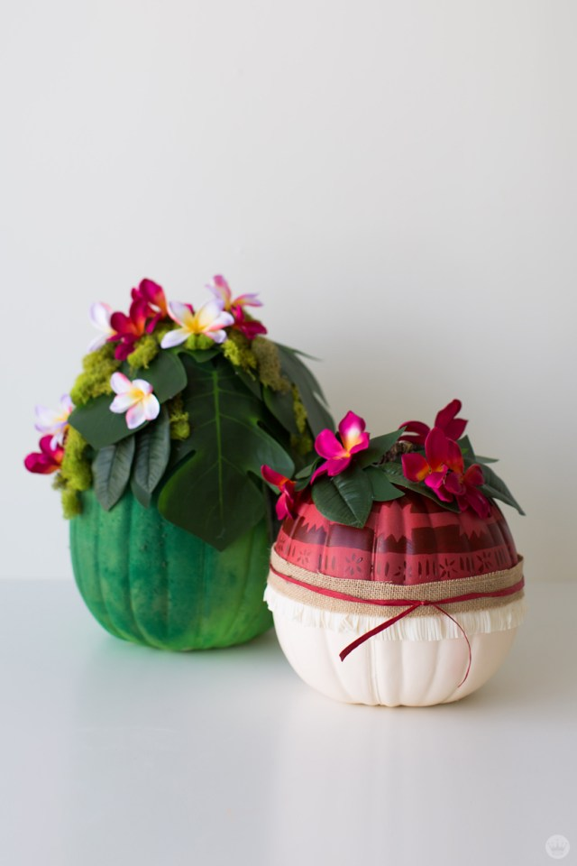 Two pumpkins decorated with tropical plants and flowers