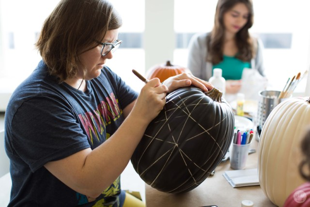 Using markers to add criss-crossed lines on a black pumpkin
